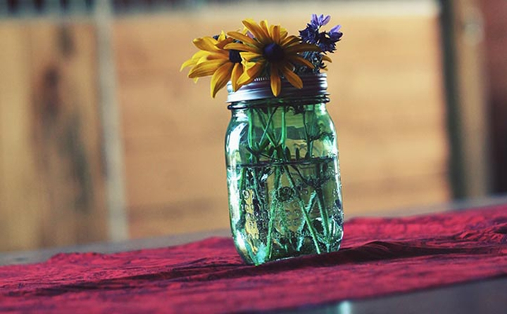 Freshen up the place by adding flowers to your candle jars
